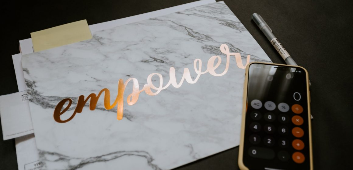 """The word """"empower"""" on top of paperwork. Sitting atop of it is a mobile phone with the calculator app open."""
