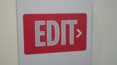"""Sign with large bold letters saying """"EDIT"""" with a small arrow to the right."""