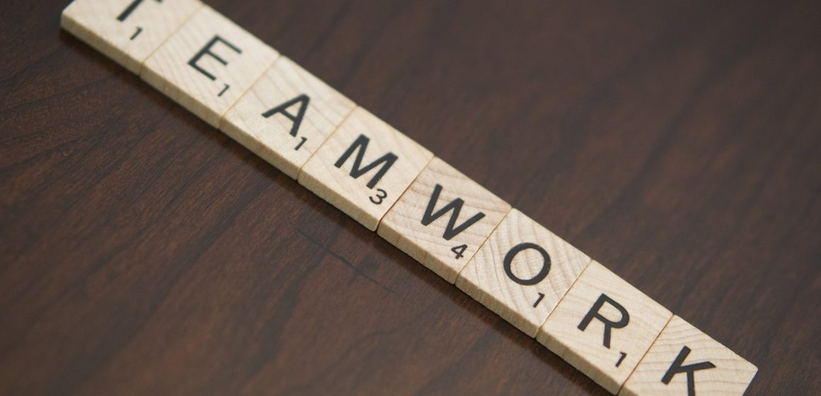 Small wooden game pieces each with a letter on it spelling TEAMWORK